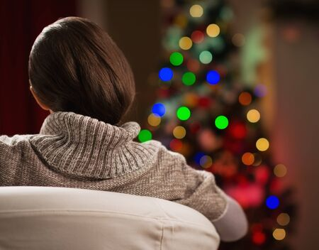 anonym: Young woman looking on Christmas tree. Rear view