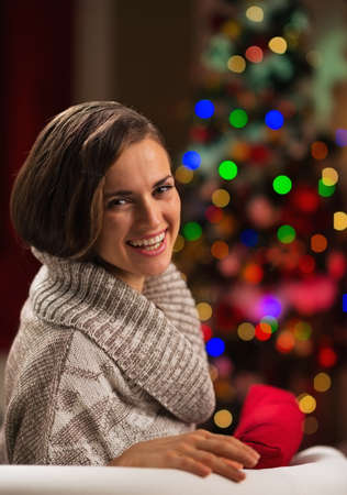 Happy young woman sitting in front of Christmas tree Stock Photo - 16710973