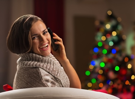 Happy young woman calling mobile in front of Christmas tree Stock Photo - 16710970