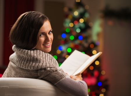 Happy young woman reading book in front of Christmas tree photo