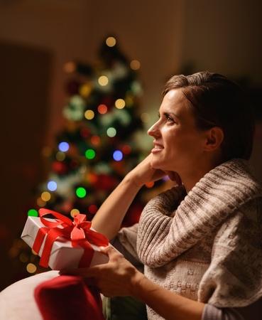 donna seduta sedia: Sognando giovane donna seduta sedia con scatola regalo di Natale Archivio Fotografico