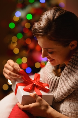 donna seduta sedia: Felice giovane donna seduta sedia e la scatola regalo di Natale di apertura Archivio Fotografico