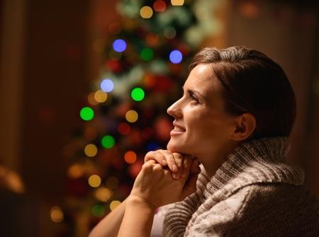 donna seduta sedia: Sognando giovane donna seduta sedia di fronte di albero di Natale