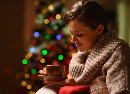 Dreaming young woman sitting chair with hot chocolate in front of Christmas tree Stock Photo
