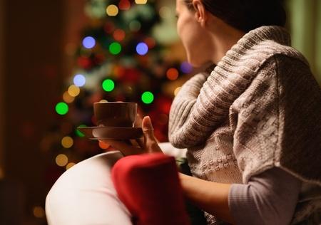 donna seduta sedia: Giovane, donna, seduta, sedia con bevande calde di fronte albero di Natale. Vista posteriore