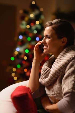 donna seduta sedia: Giovane donna seduta sedia e facendo telefonata di fronte all'albero di Natale