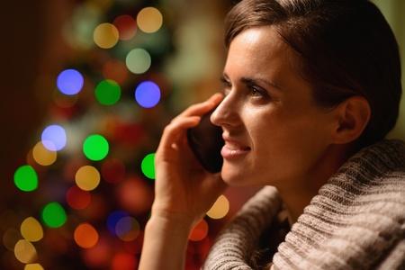 donna seduta sedia: Giovane donna seduta sedia e facendo telefonata di fronte a luci di Natale