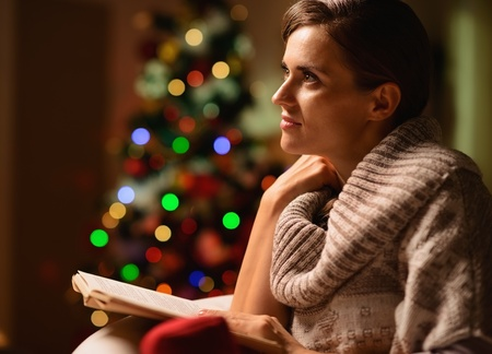 Dreaming young woman sitting chair and reading book in front of Christmas tree Stock Photo - 16710994