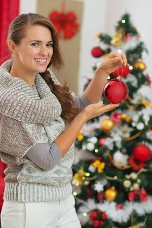 Happy young woman holding Christmas ball near Christmas tree Stock Photo - 16720087