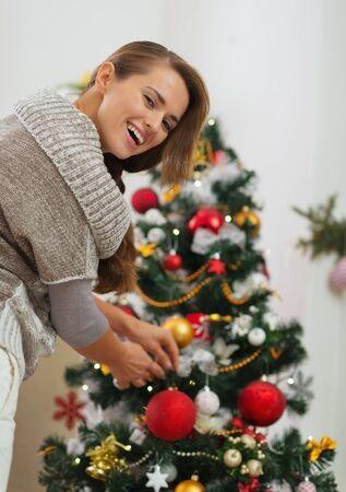 Happy young woman hanging Christmas ball on Christmas tree Stock Photo - 16720175