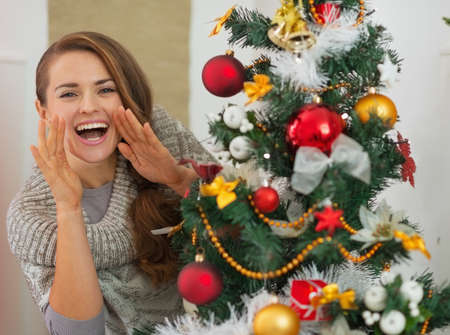 shaped hands: Happy woman shouting through megaphone shaped hands out from Christmas tree