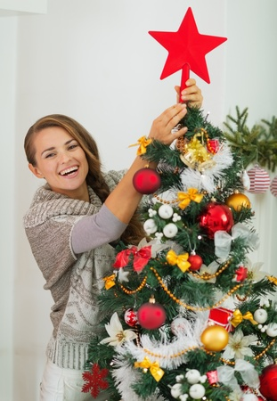 Happy young woman hanging Christmas top on Christmas tree photo