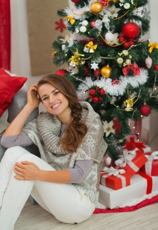 Happy young woman sitting near Christmas tree Stock Photo - 16720140