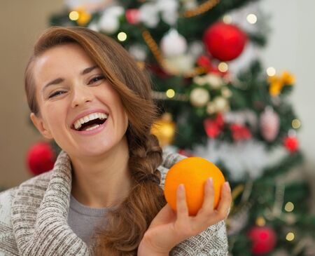 Portrait of smiling young woman with orange near Christmas tree Stock Photo - 16720179