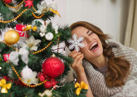 Happy woman sitting playing with Christmas tree decoration Stock Photo - 16720143