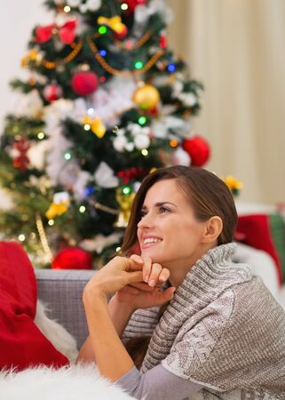 Dreaming young woman sitting near Christmas tree Stock Photo - 16720088