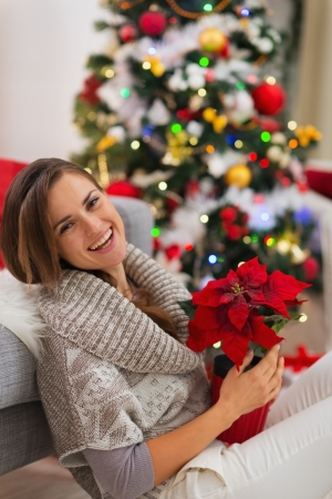 Smiling woman with Christmas rose sitting near Christmas tree Stock Photo - 16720165
