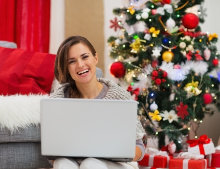 Smiling young woman with laptop sitting near Christmas tree Stock Photo - 16720171