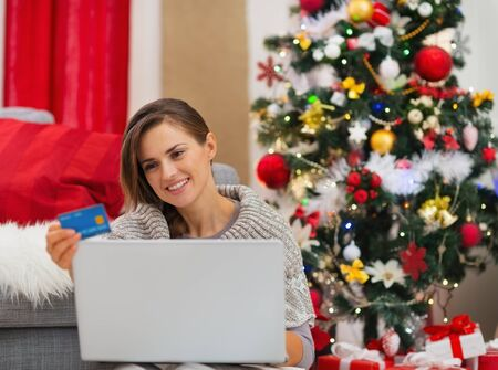 Happy young woman making online purchases near Christmas tree Stock Photo - 16720167