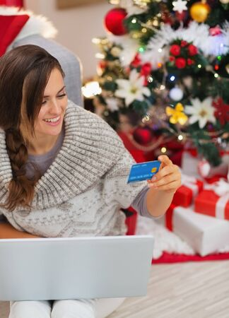 Smiling woman with laptop and credit card near Christmas tree Stock Photo - 16720071