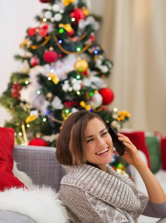 Happy young woman speaking mobile near Christmas tree Stock Photo - 16720076