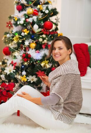 Happy young woman decorating Christmas tree Stock Photo - 16720177