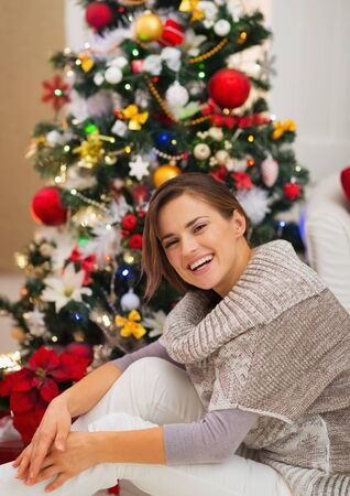 Portrait of happy young woman sitting near Christmas tree Stock Photo - 16720137
