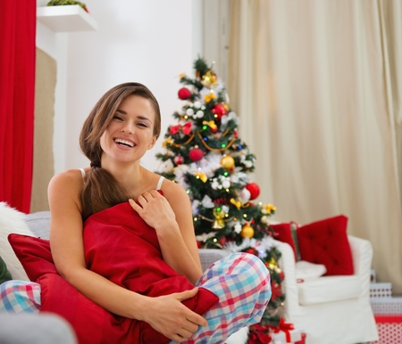 Smiling young woman in pajamas sitting on sofa near Christmas tree Stock Photo - 16720070
