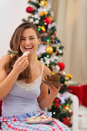 Happy young woman in pajamas eating cookies with hot chocolate near Christmas tree photo