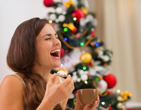 galletas de navidad: Sonriente mujer joven en pijama comiendo galletas con chocolate caliente cerca del �rbol de Navidad