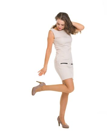 Young woman in dress adjusting shoe Stock Photo - 16882263