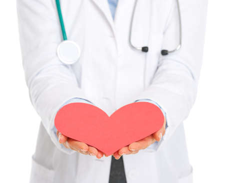outstretching: Closeup on medical doctor outstretching paper heart