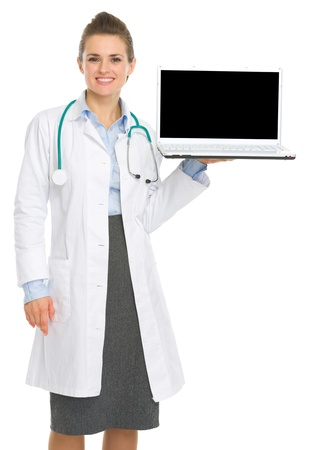 Smiling medical doctor woman showing laptop with blank screen Stock Photo - 17056180