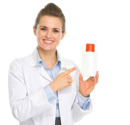 Smiling cosmetologist pointing on bottle of sunscreen Stock Photo - 17056195