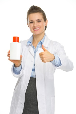 Smiling cosmetologist with bottle of sunscreen showing thumbs up Stock Photo - 17056150
