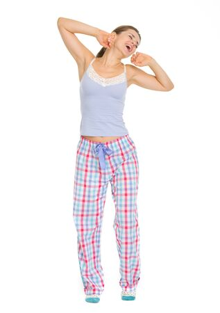 Full length portrait of young woman in pajamas stretching and yawing photo
