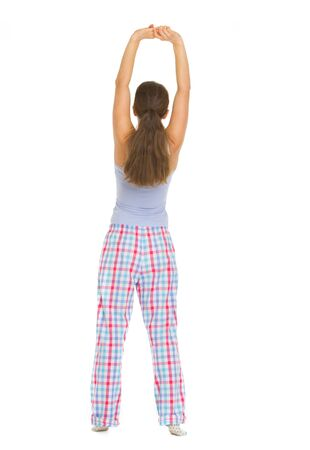 wakening: Full length portrait of young woman in pajamas stretching. Rear view Stock Photo