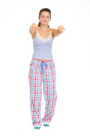 somnambulism: Full length portrait of young woman in pajamas sleep walking