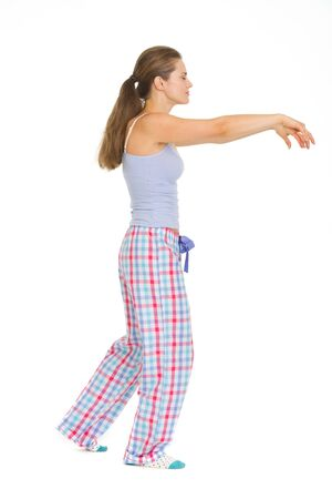 sleepwalker: Full length portrait of young woman in pajamas sleep walking