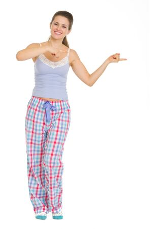 Full length portrait of young woman in pajamas pointing on copy space Stock Photo - 17137453