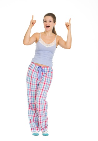 Full length portrait of young woman in pajamas pointing up on copy space Stock Photo - 17137379