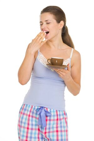 yawing: Mujer joven en pijama con la taza de caf� gui�ada despu�s de dormir Foto de archivo