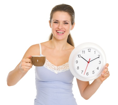 Happy young woman in pajamas with cup of coffee and clock Stock Photo - 17137437