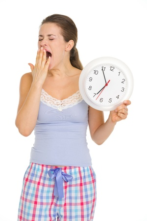 yawing: Young woman in pajamas with clock yawing after sleep