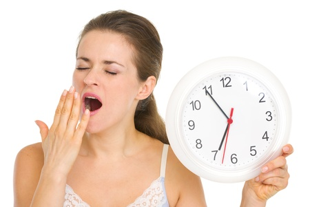 yawing: Young woman with clock yawing after sleep