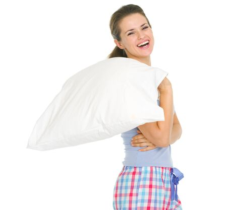Smiling young woman in pajamas holding pillow Stock Photo - 17137444