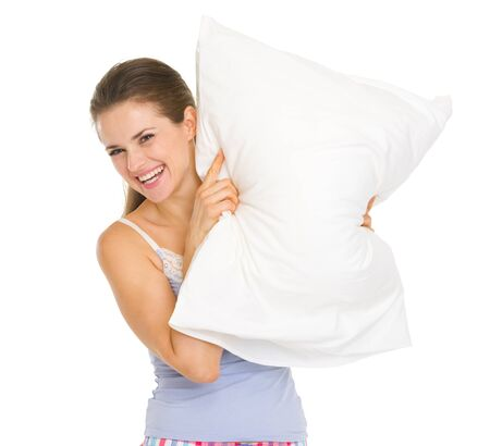 Happy young woman in pajamas looking out from pillow Stock Photo - 17137455