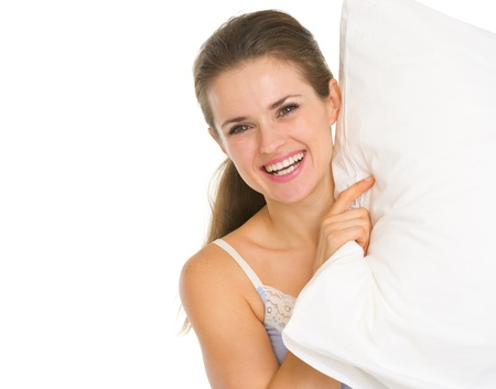 Smiling young woman looking out from pillow Stock Photo - 17137397