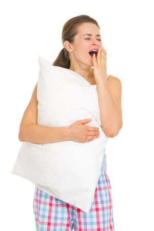 Happy young woman in pajamas with pillow yawing Stock Photo - 17137416
