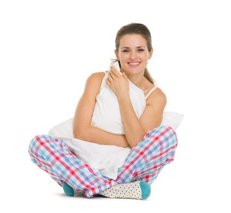 Smiling young woman in pajamas sitting with pillow Stock Photo - 17137376